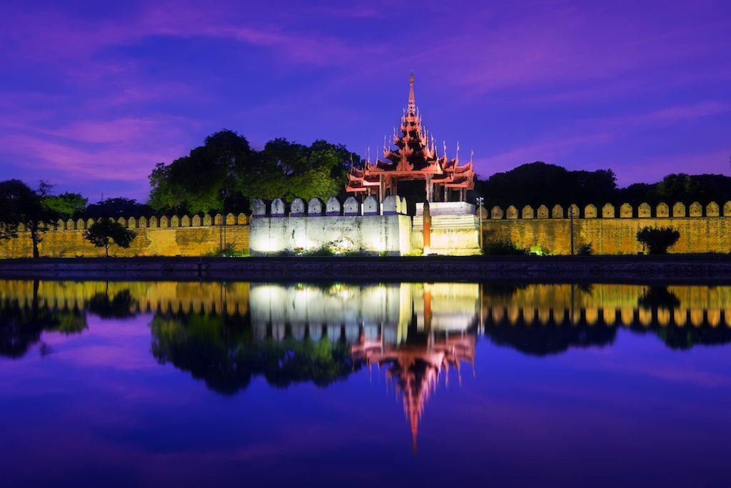 Night view of Mandalay cityscape with famous Fort or Royal Palace. Myanmar (Burma) travel landscapes and destinations