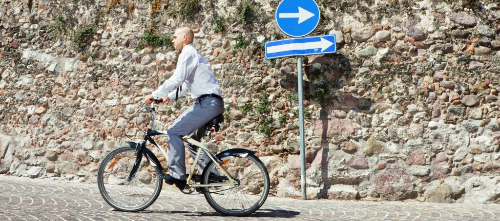A man on a bicycle going the opposite way of a directional sign.