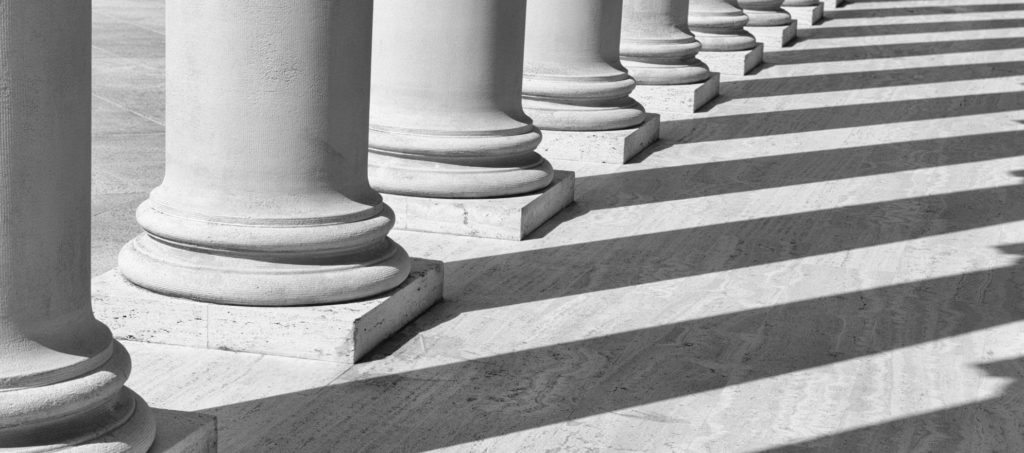 Pillars casting shadows on the ground in front of a courthouse