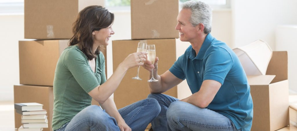 A couple sharing a champagne toast on the floor in their new house