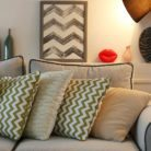 A living room with neutrals, graphic patterns and soft light