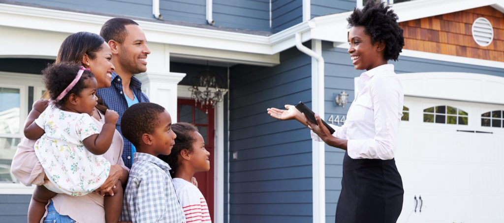 A real estate agent showing a home to a family