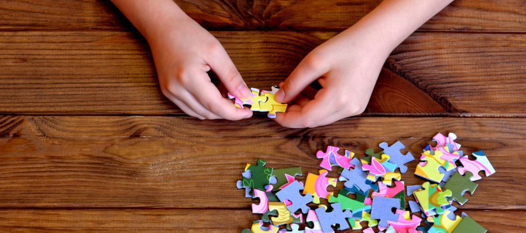A child's hands putting a jigsaw puzzle together