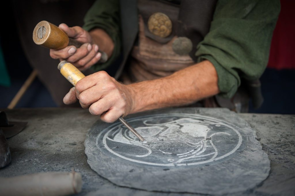 An artisan carving a plate