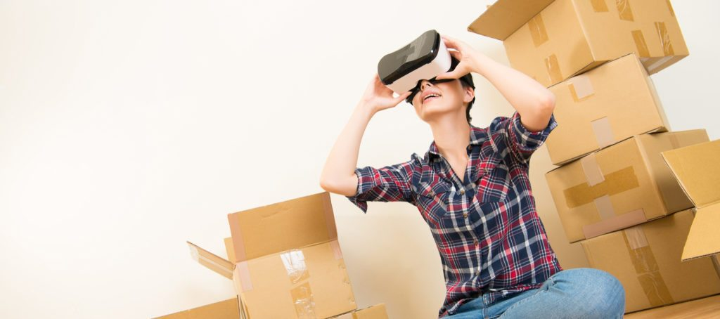 A woman looks through a virtual reality headset in the midst of boxes