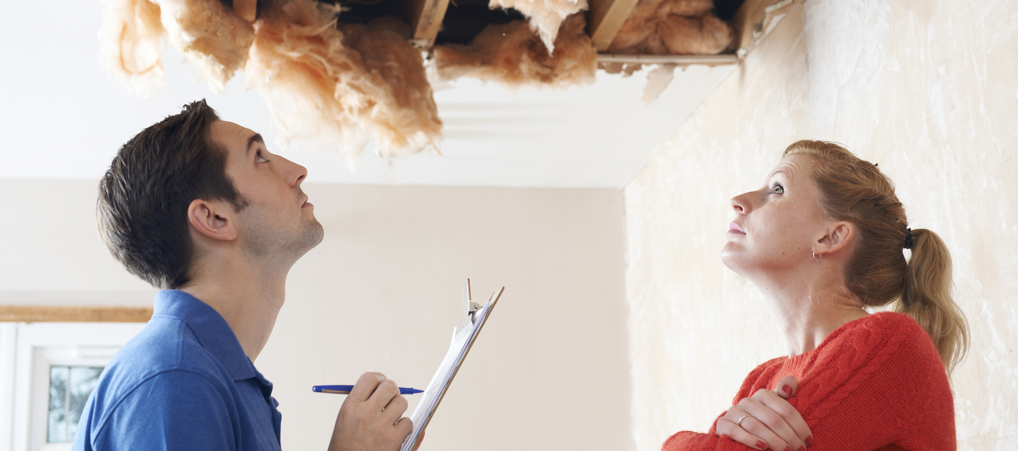 A homeowner and an inspector looking at a collapsed ceiling