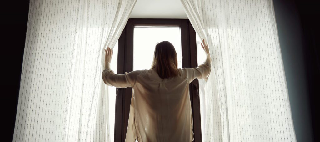 A woman opening the curtains