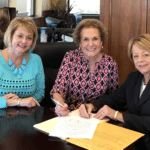 Mary Evans, D'Ann Harper and Diane Sanders signing acquisition paperwork