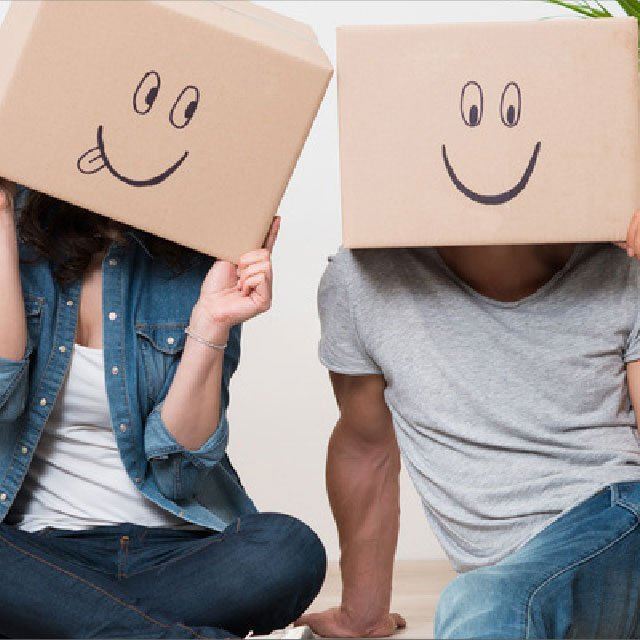 Couple with happy face boxes over heads