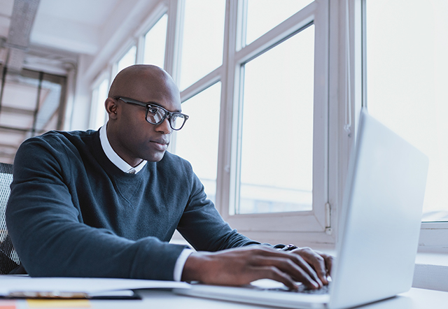 Image of african american businessman working on his laptop. Handsome young man at his desk.; Shutterstock ID 262840061; Purchase Order: 19_301792; Job: Inman comm's story; Client/Licensee: Remax