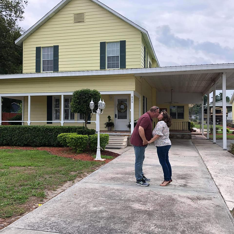 Married couple in front of new house
